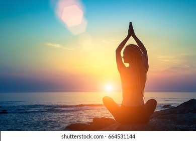Yoga silhouette. Meditation fitness woman on the ocean during amazing sunset. Healthy lifestyle.