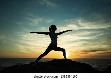 Yoga silhouette meditation girl during beautiful twilight on the sea coast.