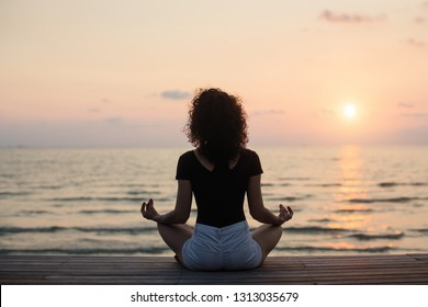 Yoga silhouette. Meditation girl on the sea during sunset.