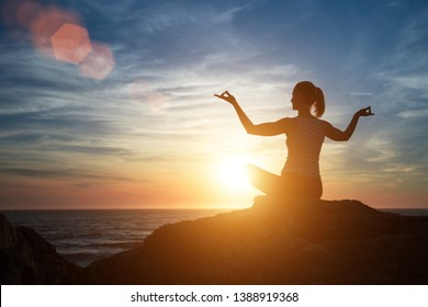 Yoga silhouette of meditation woman on the beach at amazing sunset.