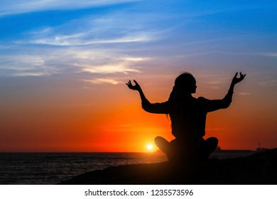 Yoga silhouette of woman meditating on the ocean beach during amazing sunset.