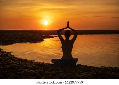 Yoga silhouette. Silhouette of woman sitting on the beach, practicing yoga. Young woman raising arms with namaste mudra during sunset golden hour. View from back. Sun reflection. Melasti beach, Bali