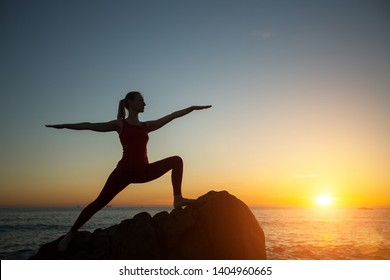 Yoga silhouette young woman doing fitness exercises on the sea beach at amazing sunset.