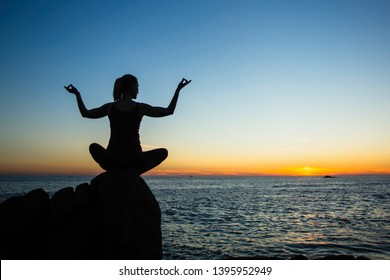 Yoga silhouette young woman on the beach amazing sunset. Relax and health.