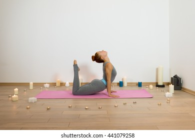 Yoga. Slim woman having yoga trainig on pink gymnastic carpet in candle lit room. Yoga concept of physical and mental health, happy living and well being
