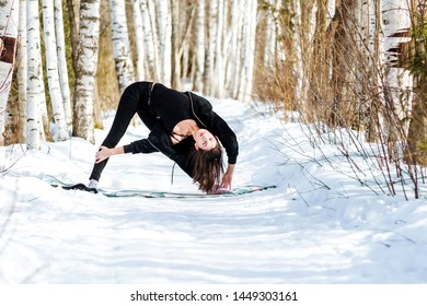 Yoga in the snow. Girl practicing yoga in the Park. Time of year winter. Snow-covered trees.