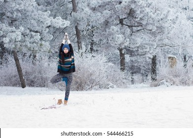 Yoga in the snow. Girl practicing yoga in the Park. Time of year winter. Snow-covered trees. Vrikshasana.
