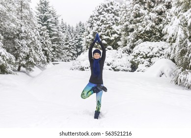 Yoga in the snow. Girl practicing yoga in the Park. Time of year winter. Snow-covered trees. Vriksasana. Standing pose- close-up.