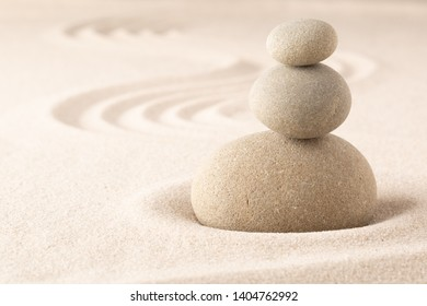 Yoga or spa wellness sandy background with round zen stone in Japanese sand garden and open copy space. Pile of stones balancing.