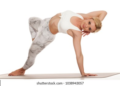 Yoga, sport, training and lifestyle concept - Young blonde woman in white sportswear doing yoga practice. Wild thing, camatkarasana