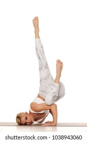 Yoga, sport, training and lifestyle concept - Young blonde woman in white sportswear doing yoga practice. Devaduuta panna asana or Fallen angel pose