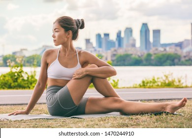 Yoga stretch exercise fit Asian woman stretching lower back for spine health on city outdoor fitness class in park. Seated spinal twist.
