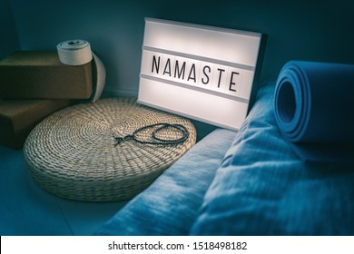 Yoga studio class sign lightbox with letters writing NAMASTE glowing in the night light with natural accessories, rubber mat, cork blocks, organic cotton strap and pillows, straw meditation pillow.