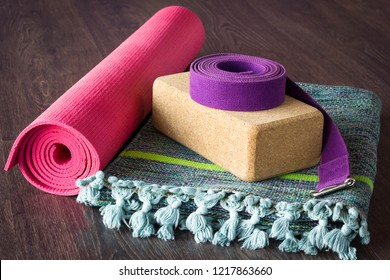 Yoga studio props selection on wooden floor. Pink mat, cork brick, purple belt and colorful cotton mat