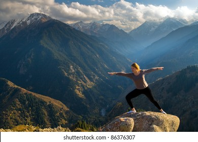 Yoga at summit with aerial view of the mountain range and peak, with sunlight