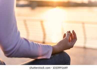 Yoga Sunset Poses.  Woman sits in lotus position zen gesturing. Concept of healthy lifestyle and relaxation. Yoga woman meditating at serene river sunset. serenity and yoga practice at sunset
