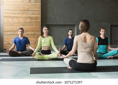 Yoga teacher and beginners in class, making asana exercises. Lotus pose. Healthy lifestyle in fitness club. Stretching with coach
