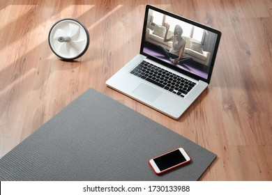 Yoga teacher online. Closeup of equipment for online fitness at home: exercise mat, smartphone, laptop, health progress app. Workout or yoga online while quarantine and self isolation. Copy space