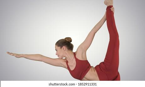 Yoga teacher practising pose dandayamana dhanurasana on gradient