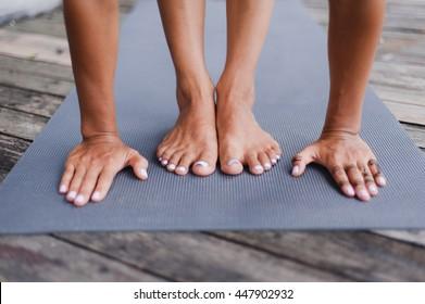 Yoga teacher put her hands near her feet on the floor
