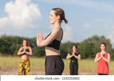 yoga teacher and students practicing yoga outdoors