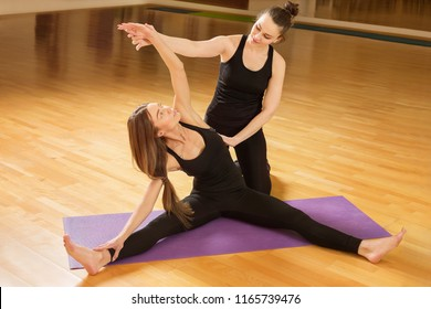 Yoga teacher is training young woman stretching her hand at gym. Fitness workout.