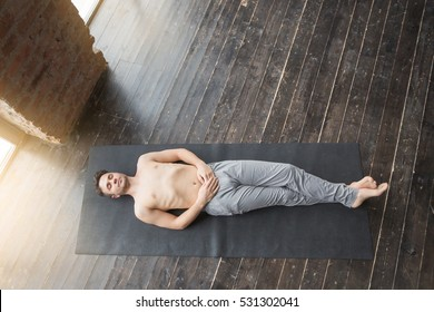 Yoga. Top view of young men meditating on a wooden floor and lying in Shavasana pose. View from above of attractive yogi working out at urban loft studio, doing yoga exercise on black mat. Lifestyle