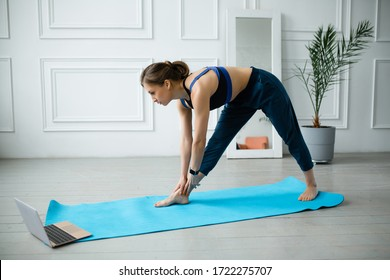 Yoga trainer advises on a laptop video how to do stretching exercises on the back of the thigh and back muscles.