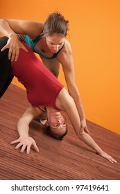 Yoga trainer helping student perform yoga stretching