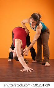 Yoga trainer helping young woman perform exercises