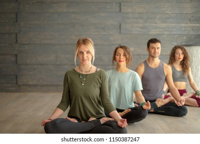 Yoga training indoors. Close up of meditating people sitting on the floor with crossed legs and closed eyes, full-size portrait over calm grey background. Harmony and Healthy Lifestyle Concept.