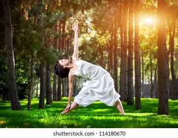 Yoga utthita trikonasana triangle pose by woman in white costume on green grass in the park around pine trees