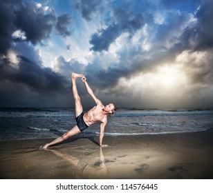 Yoga vasisthasana side plank pose by fit man on the beach near the ocean at sunset background