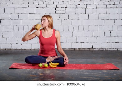 Yoga Vegetarianism. Girl drinks smoothies. Woman having a yelloy juice in the hall after her yoga practice. concept of healthy life.
