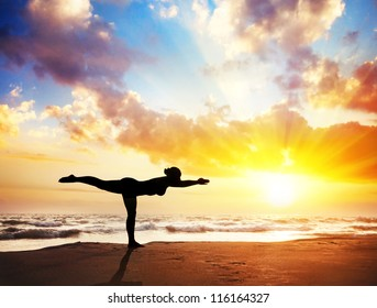 Yoga virabhadrasana III, warrior pose by woman in silhouette with sunset sky background. Free space for text