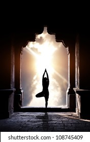 Yoga vrikshasana tree pose by man silhouette in old temple arch at dramatic sunset sky background. Free space for text