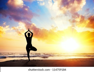 Yoga vrikshasana tree pose by woman in silhouette with sunset sky background. Free space for text