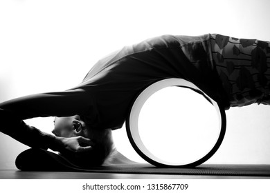 Yoga wheel girl. Side view of a young woman practicing pigeon yoga pose with a help of yoga wheel, black and white
