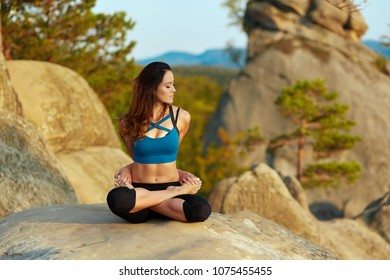 Yoga woman. Attractive young woman meditation on top of a mountain on a warm sunny morning nature outdoors meditation asana yoga healthcare wellness recreational sunrise happiness positivity