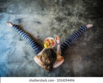 Yoga Woman with Chia Fruit plate on the floor in bird view