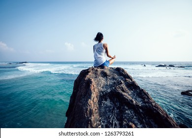 Yoga woman clothing in white meditation at the seaside cliff edge