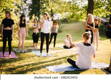 Yoga woman coach welcomes his students and gives instructions in park at dawn. Guru sits on yoga mat among his followers. Beginning of retreat outdoors in sunny morning. Women friendly community