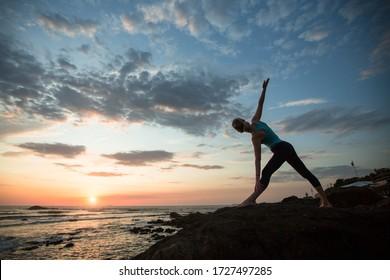 Yoga woman doing exercises on the atlantic ocean coast at twilight. Porto, Portugal.