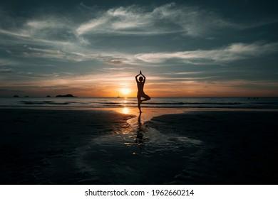 Yoga woman doing meditation on the ocean beach.