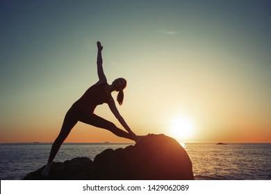 Yoga woman doing morning exercises on the sea beach.