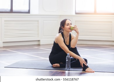 Yoga woman drinking water and eat apple on black yoga mat in fitness class. Healthy lifestyle concept