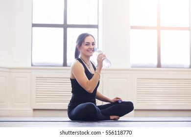Yoga woman drinking water while holding yoga mat in fitness class. Healthy lifestyle concept