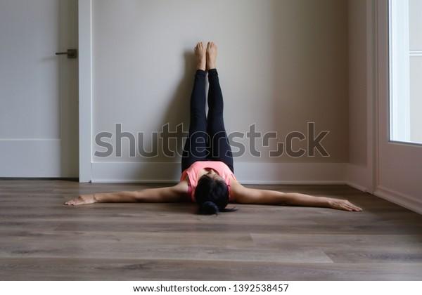 壁でくつろぐヨガの女性、認識できない人