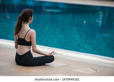 Yoga woman hand in lotus meditation pose at swimming pool.