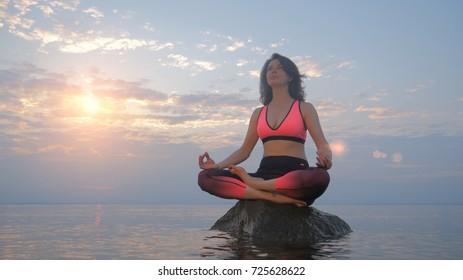 Yoga woman in lotus pose on rock in sea water at sunrise